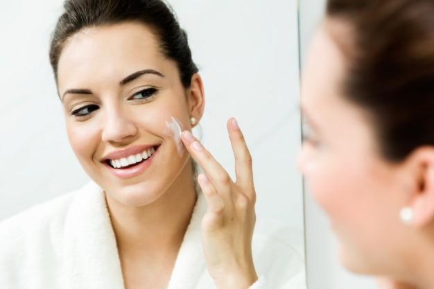 joven-mujer-cuidado-ella-piel-posicion-cerca-espejo-bathr_1301-3375