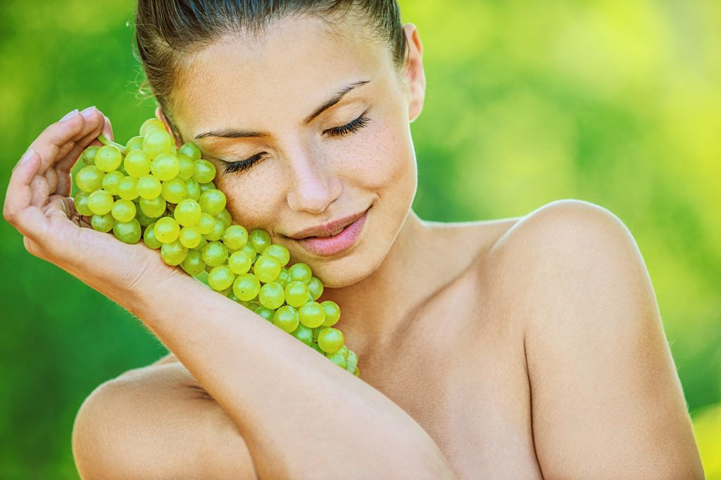 woman with bare shoulders holding grapes