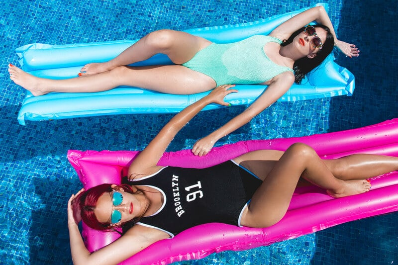 Canva Two Woman Laying Down on Pink and Blue Floaters 1 1